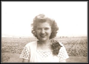 May 1945 - Marilyn Wanda Wisian Graduation from Karl Wiegand School in Uhland Cotton field in the background. The town of Uhland would be over her right shoulder and the new Uhland Elementary School over her left shoulder – to the viewers' right – out there in the cottonfield!